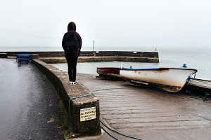 Woman wearing casual clothes standing at harbor in Irish coast
