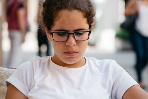 Girl wearing glasses reading sitting in the street