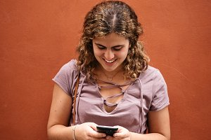 Beautiful young woman smiling texting on her smart phone