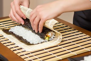 Woman chef rolling up japanese sushi