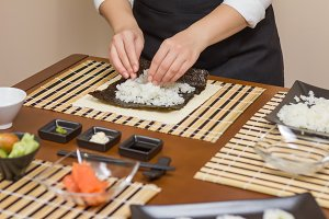 Chef filling japanese sushi rolls