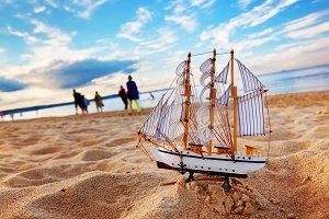 Ship model on summer beach at sunset