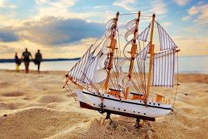 Ship model on summer beach at sunset