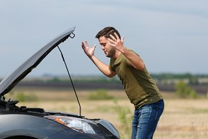 Photo of frustrated man next to broken car with open hood