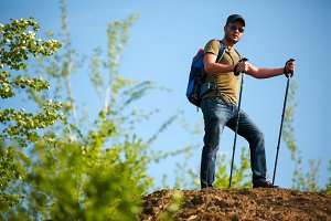 Portrait of man with backpack and walking sticks on hill