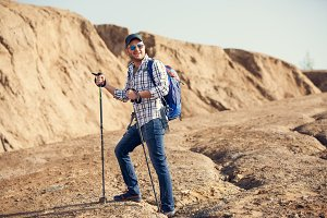 Photo of smiling tourist man with walking sticks on hill