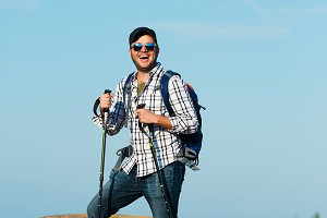Photo of young tourist with sticks for walking on hill