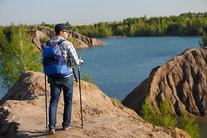 Photo from back of tourist man in cap with walking sticks on mountain hill near lake