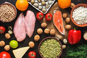 Balanced dietary products. The concept of healthy eating. Background of a healthy meal. Fruits, vegetables, salmon, chicken fillet, cereals. The view from above, flat lay.