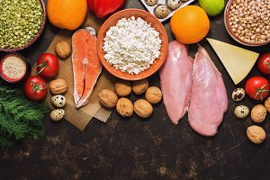 Background with healthy food. Red fish, chicken fillet, vegetables, fruits, cereals, dairy products, quail eggs. Top view, copy space.