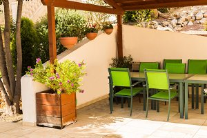 Comfortable furniture, tables and chairs on a spacious terrace in the summer