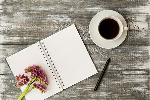 Top view of a diary or notebook, pencil and coffee and a purple flower on a gray wooden table. Flat design.