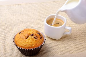Perfect morning breakfast with Delicious homemade cupcakes with raisins, chocolate chips, espresso coffee in white cup and milk on textile background. Muffins.