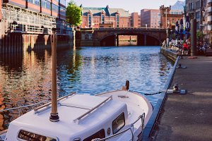 White pleasure boat at a pier in Nikolaifleet churchtower St. Nikolai, Hamburg,Germany