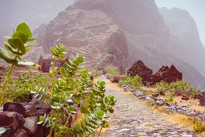 Hiking route to Ponta do Sol over amazing Aranhas valley with left houses in arid climate. Huge mountains of coastline and old local stone houses at the foot. Santo Antao Island, Cape Verde