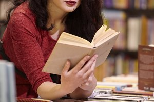one young woman, surrounded with books, reading a book, bookstore, indoors.