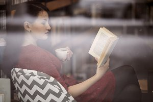 one young woman, reading a book in a bookstore sitting in sofa, holding coffee cup. shoot thought window reflections.