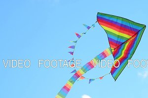 Rainbow kite flying against blue sky