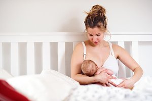 Young mother breastfeeding her newborn baby son, home bedroom