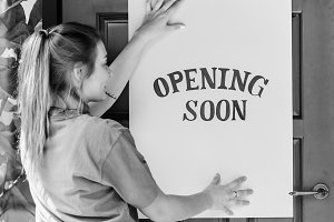 Woman putting opening soon sign