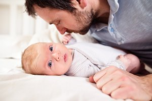 Baby boy lying on bed, held by his father