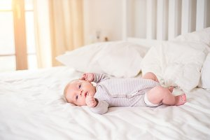 Little baby boy lying on bed in onesie, white bedroom