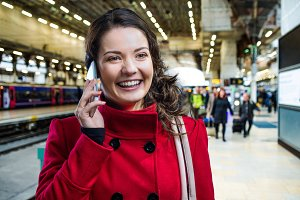 Woman in red coat on train station talking on phone