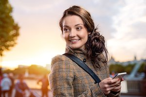 Woman in brown coat with smart phone in sunny park