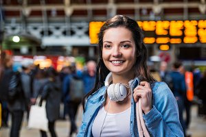 Tourist girl in denim shirt with earphones. Train station.