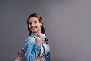 Tourist girl in denim shirt with handbag, studio shot