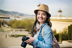 Tourist girl in denim shirt with camera, sunny city