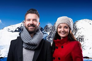 Beautiful young couple in winter clothes in winter mountains