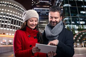 Couple with tablet in winter clothes in night city