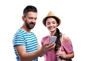 Couple in summer clothes with smartphone, taking selfie
