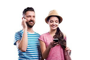 Couple in summer clothes with smartphones, texting, phone call