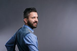 Hipster businessman in blue shirt, studio shot, gray background