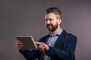 Hipster businessman with tablet, studio shot, gray background