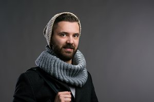 Man in winter coat, scarf and beanie. Studio shot