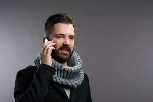 Man in winter clothes with smartphone, making phone call