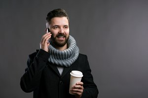 Man in winter clothes holding coffee cup and smartphone