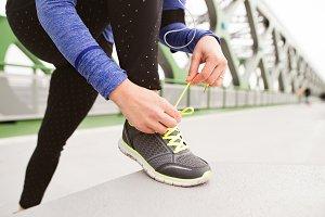 Unrecognizable runner in the city tying shoelaces on steel bridg