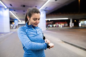 Young woman in blue sweatshirt running in the night town