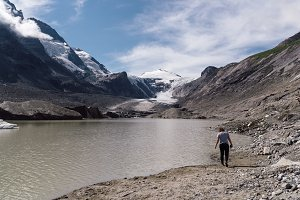 Rear view of woman on lake by glacier