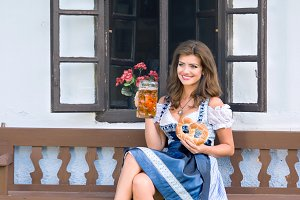 Woman in traditional bavarian dress holding beer and pretzel