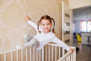 Little girl with braids hanging above white baby crib