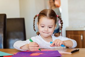 Cute little girl with braids drawing on colorful papers