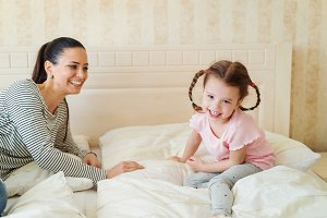 Mother with daughter on a bed in their bedroom