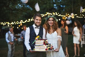 Bride and groom holding a cake at wedding reception outside in the backyard.