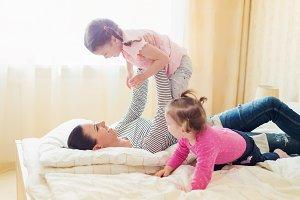 Mother having fun with her daughters in her bedroom