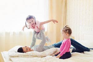 Mother having fun with her daughters in her bedroom